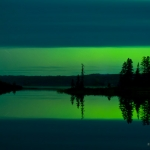 A Slice of Aurora: Cloud cover allows a slice of northern lights to shine over Devil Track Lake. Minnesota.