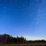 Stars over Mud Creek: The stars circle around the north star over Mud Creek. A slight glow of northern lights on the horizon. Minnesota.