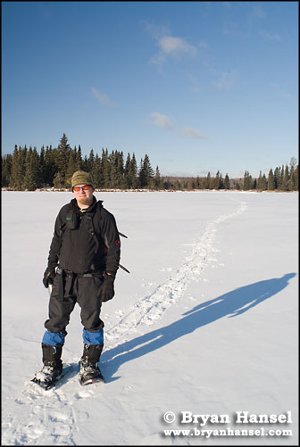 Guide snowshoeing across a lake