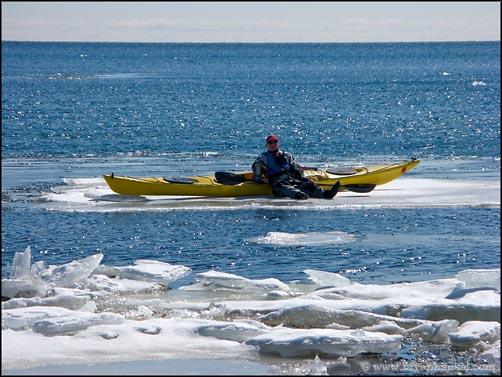 Kayaker standing on ice with a kayak