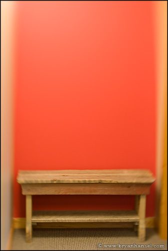 Stool up against a red wall.