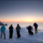 Photographers on Lake Superior's shoreline taking sunrise photos during a photography workshop.
