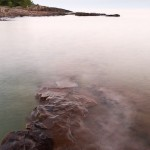 Some of the oldest lava rock falls away into Lake Superior. The waves wash over it at sunset. Grand Marais, MN.