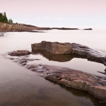 Water flows and weaves around rocks on Artist's Point at sunset. Grand Marais, MN