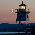 A crescent moon rests near the Grand Marais lighthouse before it falls behind the Sawtooth Mountains.