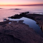 The sunrise reflected in Lake Superior and a still puddle on Artist's Point.