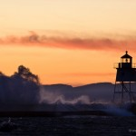 Grand Marais Lighthouse and breakwall with waves crashing over.