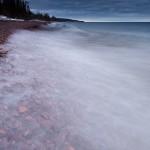 Waves wash over stones on Lake Superior.