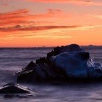 At sunset waves wash around an ice-covered rock. The Sawtooth Mountains are in the distance. Lake Superior, Minnesota.