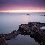 A rain water pool next to Lake Superior's smoothed waters at sunrise. Artist's Point. Grand Marais, Minnesota.