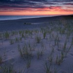 Sunrise in Grand Marais, MIchigan over beach grass and sand dunes.