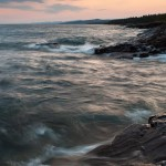 Looking down the shoreline from Grand Marais, MN as some waves wash up onto the basalt shoreline.