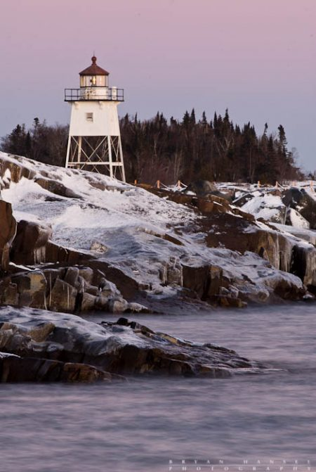The Grand Marais Lighthouse in winter. The Belt of Venus turns the sky pink.