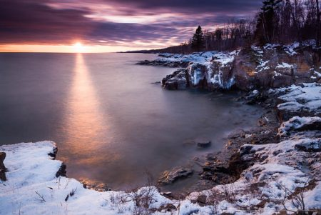 The sun sets over Lake Superior at Butterwort Cliffs SNA in winter. Minnesota.