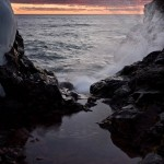 A pool of water collects behind a basalt constriction. Lake Superior's waves splash in the background.