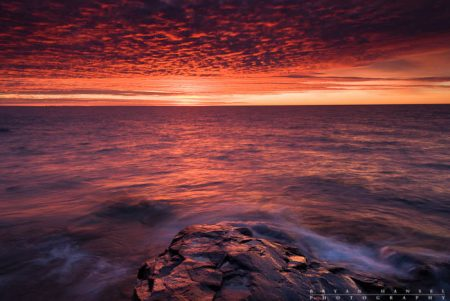 The sun sets the sky on fire over Lake Superior.