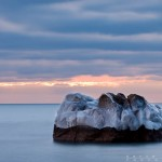 A small icy island on Lake Superior at sunrise.