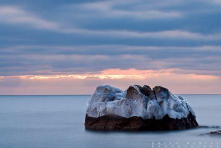 A small icy island on Lake Superior at sunrise.
