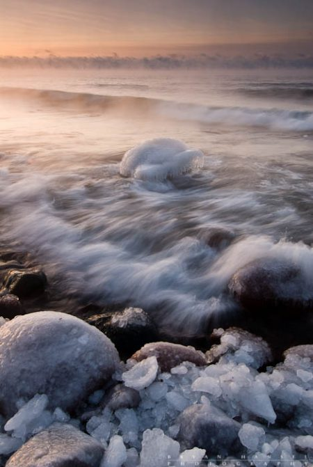 Orange and Icy 5: Sea smoke rises from Lake Superior during this sub-zero morning. The sun rises over an icy shoreline and waves roll in. 120120-38