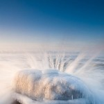 Rock, Ice and Waves: Waves splash over an ice-coated rock on Lake Superior. 120120-46