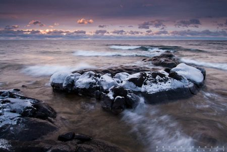 Winter on Superior: Waves and ice wash over and coat the basalt of Lake Superior's shoreline. 120128-45