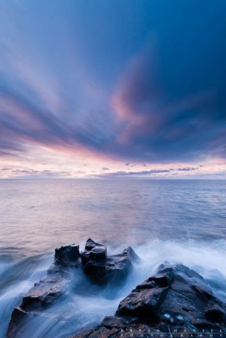 Waves in the Clouds I: Wisps of clouds light up blue and pink at sunrise near Grand Marais, MN.
