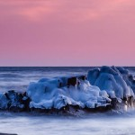 Waves wash around an ice-coated rock under a pink sky. Lake Superior.