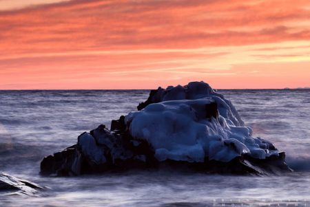 An ice-coated rock awash with waves under a reddish-orange sky.