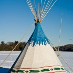 The moon rises above a tipi on East Bearskin Lake. Minnesota.