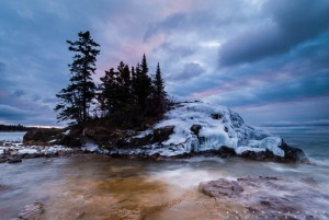 The sunrise turns the clouds purple and blue over an icy island on Lake Superior. Minnesota.