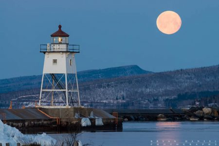 The moon hovers over the Sawtooth Mountains behind the Grand Marais lighthouse. Lake Superior.