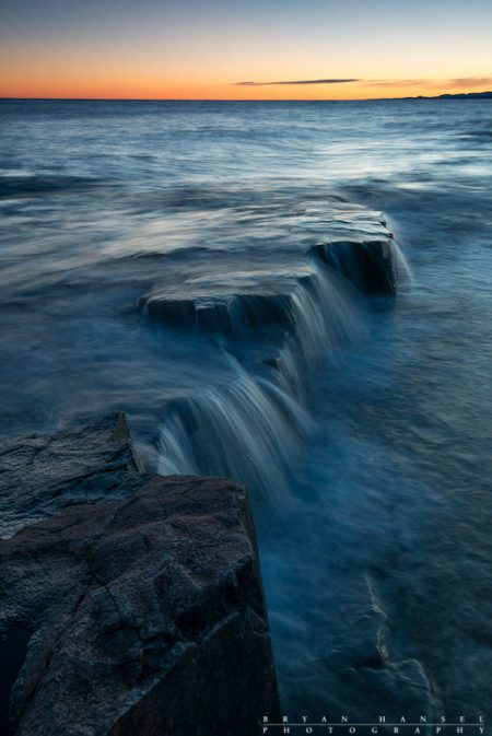 waves flow over basalt edge