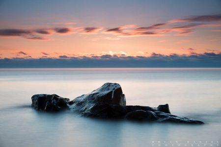 a rocky island on lake superior at sunrise