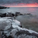Snow from brief snow flurries covers the basalt of Artist's Point. The sunrise creates a sun pilar and a pink sky. Grand Marais, Minnesota.