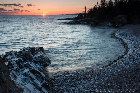 The sun sets over Lake Superior and over a small pocket cobblestone beach surrounded by basalt. Cook County, Minnesota.