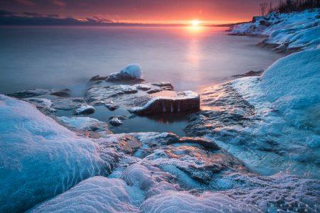 The sun sets over frozen Lake Superior shoreline in Butterwort Cliffs SNA, Cook County, Minnesota.