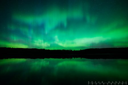 northern lights reflecting in mink lake