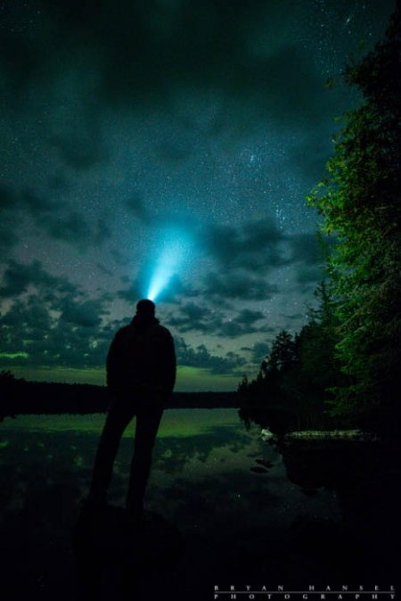 person with headlamp under northern lights
