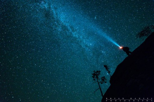 person standing on a cliff under the Milky Way with a headlamp on