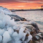 The first ice of the season clings to and coats the Grand Marais harbor shoreline. The lighthouse lights its first light during sunset. Cook County, Minnesota.
