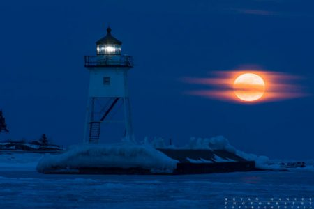the crow moon rises behind the Grand Marais lighthouse