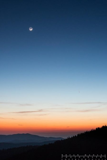 The crescent moon hangs in the sky above the Smoky Mountains.