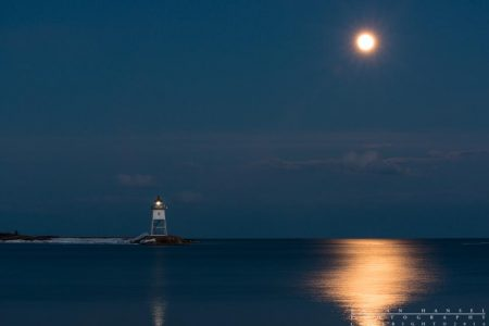 full pink moon rising behind the grand marais lighthouse