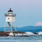 full pink moon sets behind the grand marais lighthouse
