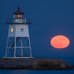 The moon rises next to the Grand Marais lighthouse. Lake Superior, Minnesota.