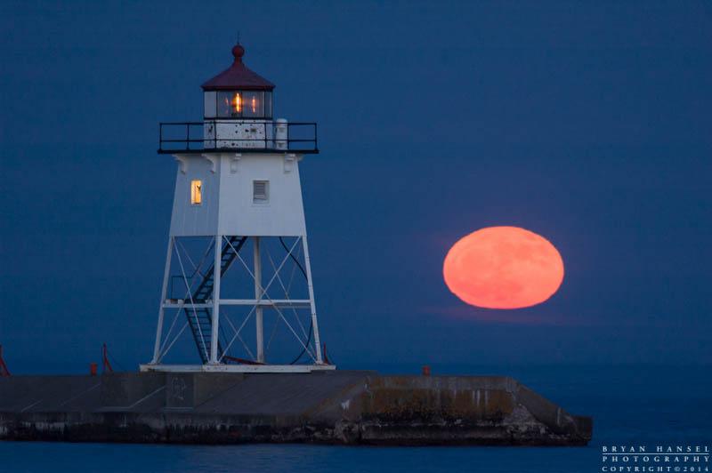 The moon rises next to the Grand Marais lighthouse. Lake Superior, Minnesota.