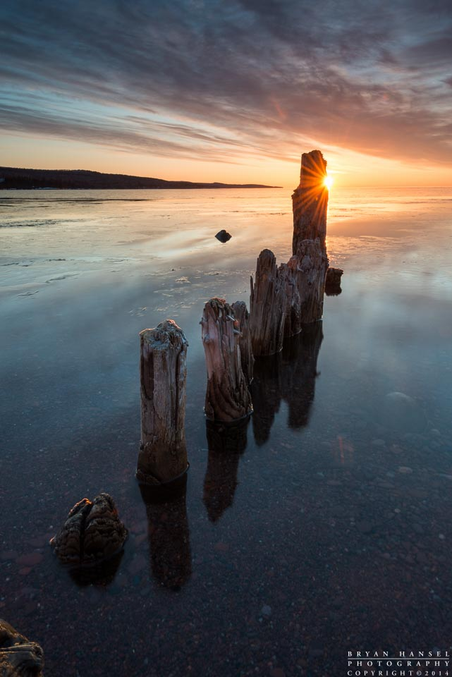 The sun rises over Lake Superior on an early spring day. Frazil ice coats the surface of the calm East Bay. Old pilings reflect in the water. Grand Marais, Minnesoa.