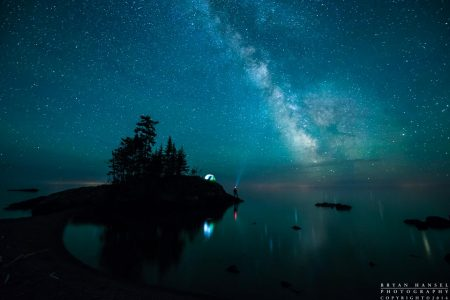 The Milky Way over Lake Superior, the tombolo and a tent and person with a headlamp. Grand Marais, Minnesota.