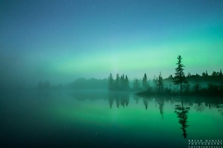A band of northern lights burns through the light fog and reflects in Devil Track Lake. Cook County, Minnesota.