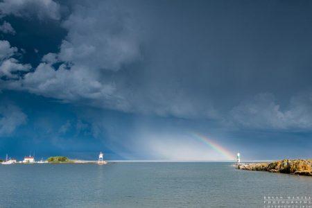 a rainbow and storm blows over Grand Marais